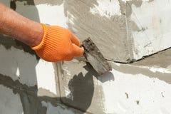 Maurermannarbeitskraft in den orange Handschuhen, die Block mit Kelle installieren Stockfotografie