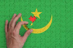 Mauritania flag is depicted on a puzzle, which the man`s hand completes to fold.  vector illustration