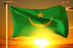 Mauritania flag weaving on the beautiful orange sunset with clouds background. Mauritania flag weaving on the beautiful orange sunset background royalty free stock photo