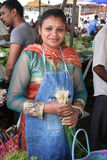 Mauritian Woman - Market Scene. Portrait: Smiling woman in Indian dress and apron selling scallions on a street market on the isle of Mauritius.The country is Royalty Free Stock Photo