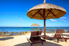Mauritius beach. Beach beds, umbrella and jetty on the beach in Mauritius Island Stock Photography