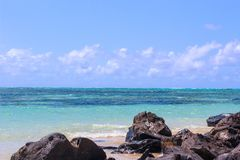 Mauritius beach, volcanic black rock with perfect skies royalty free stock photo