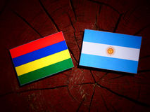 Mauritius flag with Argentinian flag on a tree stump. Mauritius flag with Argentinian flag on a tree stump Royalty Free Stock Photos