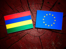 Mauritius flag with EU flag on a tree stump isolated. Mauritius flag with EU flag on a tree stump Royalty Free Stock Image