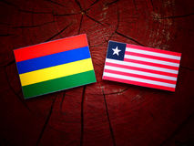 Mauritius flag with Liberian flag on a tree stump isolated. Mauritius flag with Liberian flag on a tree stump Stock Photography