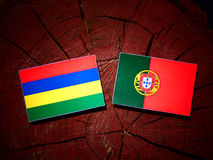 Mauritius flag with Portuguese flag on a tree stump isolated. Mauritius flag with Portuguese flag on a tree stump vector illustration