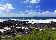 Mauritius. Steenachtige kust tegen de bewolkte hemel stock foto's