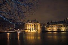 Mauritshuis die van DE Hofvijver in Den Haag bij nacht wordt gezien, die door sneeuw wordt behandeld. Stock Fotografie