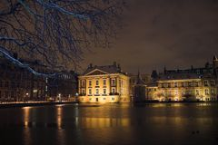 The Mauritshuis seen from de Hofvijver in the Hague at night, covered by snow. stock photography