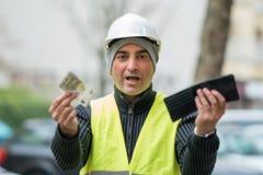 Maus momentos: trabalhador da construção pobre e sua carteira vazia imagens de stock