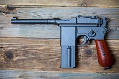 Mauser, old German pistol gun. On aged boards Royalty Free Stock Photography