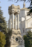 Mausoleum with columns at Monumental Cemetery, Milan. View of big mausoleum with four columns among trees at large monumental Cemetery in town, shot in bright Stock Photo