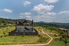 Mausoleum at domain Raja Tombs, Madikeri India. Madikeri, India - October 31, 2013: Small white and gray mausoleum, set in green garden of domain Raja Tombs royalty free stock image