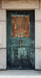 Mausoleum Door. An old and rusted mausoleum door with round metal door handle and scrollwork.  This was taken at a cemetery in Ludington, Michigan Royalty Free Stock Image