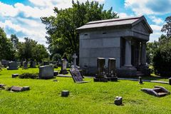Mausoleum in Graveyard with Scattered Headstones Stock Images