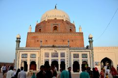 Mausoleum shrine tomb of Sufi saint Sheikh Bahauddin Zakariya Multan Pakistan. Multan, Pakistan - September 15, 2016: Worshippers mill around the courtyard of stock photography