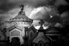 Mausoleum and Tombstones. Black and white image of a stone mausoleum and tombstones iin an ancient cemetery in France. Image has photo grain effect added royalty free stock images