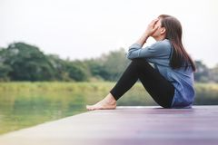 Mauvais concept de jour Femme de tristesse s'asseyant par la rivière photographie stock