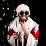 Mauvais rastoman Santa Claus tenant le sac avec des cadeaux et rayant sa barbe sur le fond de l'arbre de Noël Photographie stock