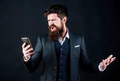 Mauvais retour de client homme barbu fâché avec le smartphone Hippie caucasien brutal Homme d'affaires dans le costume en ligne e images stock
