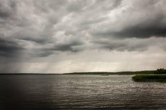 Mauvais temps foncé avec les nuages et la pluie sur un lac images stock