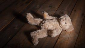 Mauvais traitement à enfant Le nounours concernent le plancher, fond en bois foncé photographie stock libre de droits