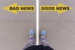Mauvaise nouvelle, flèches des textes de bonnes actualités sur l'au sol d'asphalte, pieds et chaussure Photographie stock libre de droits