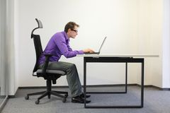 Mauvaise position d'assise d'homme d'affaires myope à l'ordinateur portable Images libres de droits