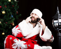 Mauvaise Santa Claus brutale a dissatisfait le téléphone parlant et sélectionner son nez, sur le fond de l'arbre de Noël images libres de droits