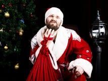 Mauvaise Santa Claus brutale tenant le sac avec des cadeaux et rayant sa barbe sur le fond de l'arbre de Noël Photos stock
