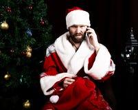 Mauvaise Santa Claus brutale tenant le sac avec les cadeaux et le téléphone parlant mécontent sur le fond de l'arbre de Noël Photographie stock libre de droits