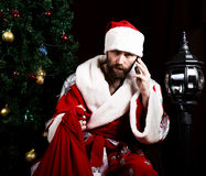 Mauvaise Santa Claus brutale tenant le sac avec les cadeaux et le téléphone parlant mécontent sur le fond de l'arbre de Noël Images libres de droits