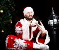 Mauvaise Santa Claus brutale tenant le sac avec les cadeaux et le téléphone parlant mécontent sur le fond de l'arbre de Noël Photos libres de droits