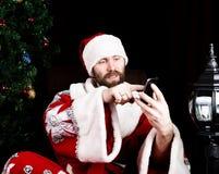 Mauvaise Santa Claus brutale tenant le sac avec les cadeaux et le téléphone parlant mécontent sur le fond de l'arbre de Noël Photo stock