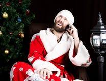 Mauvaise Santa Claus brutale tenant le sac avec les cadeaux et le téléphone parlant mécontent sur le fond de l'arbre de Noël Image stock