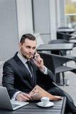 Mauvaises nouvelles Jeune homme bel parlant au téléphone dans un costume Photographie stock libre de droits