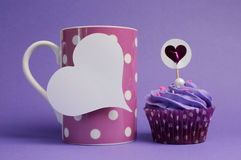 Mauve purple decorated cupcake with pink polka dot coffee mug Royalty Free Stock Image