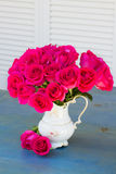 Mauve roses in vase on blue table Royalty Free Stock Photography