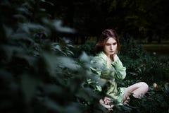 Mavka En härlig kvinna i en grön klänning går till och med skogen Arkivbild