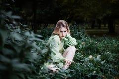 Mavka En härlig kvinna i en grön klänning går till och med skogen Royaltyfri Bild