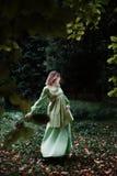 Mavka En härlig kvinna i en grön klänning går till och med skogen Royaltyfria Foton