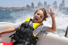 Max in Boat. Boy sitting ib moving boat holding up a peace sign stock photography