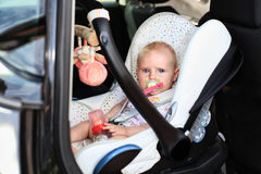 Maxi cosi baby safety. Cute little baby girl is sitting in her maxi cosi. her safety guard in a car Stock Image