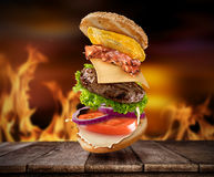 Maxi hamburger with flying ingredients Stock Photography