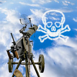 Maxim machine gun is pointed in a blue sky. With a skull and bones in the clouds royalty free stock image