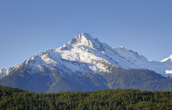 Maxima av Tantalusen spänner på det sydliga slutet av de kust- bergen av British Columbia, Kanada mot blå himmel Arkivbild