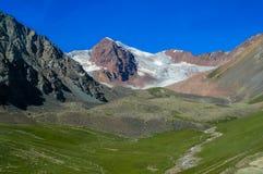 Maxima för bergdalsnö bak gröna kullar royaltyfri fotografi