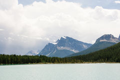 Maxima för stenigt berg som står högt över vintergrön skog och sjön Royaltyfri Bild