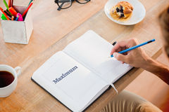 Maximum against man writing notes on diary Royalty Free Stock Images