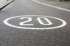 Maximum snelheidteken op een Stedelijke Weg die van Cobbled wordt geschilderd Royalty-vrije Stock Foto